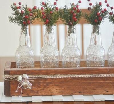 Bottiglie in vetro trasparenti e bacche rosse su una semplice cassetta in legno