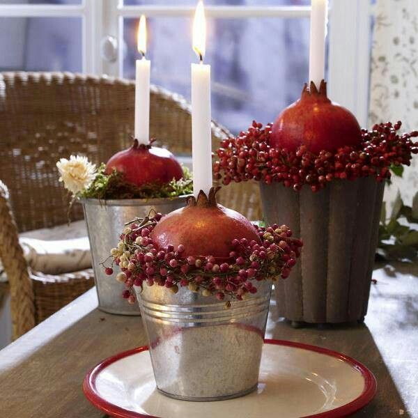 Tanti vasi diversi con melagrane e candele.