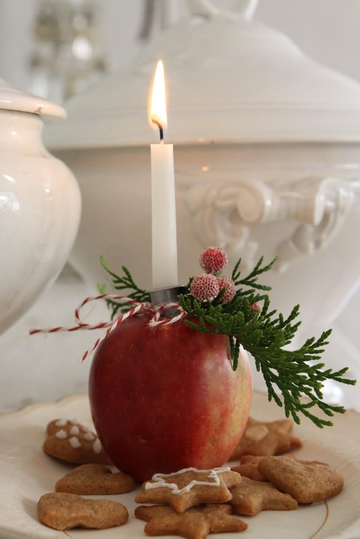 Una mela e un rametto di cipresso come portacandela
