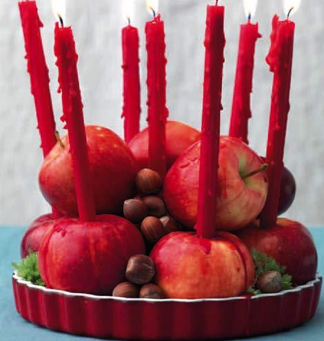 Una tortiera rossa, mele e candele per un centrotavola di grande effetto
