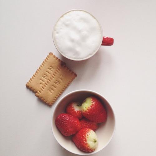 La semplicità di una schiuma di latte in tazza rossa e una coppa di fragole